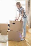 妇女包装纸板箱在家 免版税库存图片