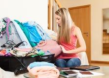 妇女包装衣裳和辅助部件到手提箱里 免版税图库摄影