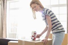 妇女包装移动的箱子在家 免版税库存照片