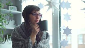 妇女包裹了在窗口基石的格子花呢披肩饮用的茶 影视素材