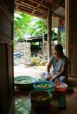 妇女包裹圆柱形糯米糕。NHON  免版税库存照片