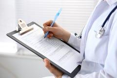 妇女医生在医院的工作 年轻女性医师写处方或填装医疗形式,当参加时 免版税库存照片