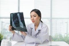 妇女医生在看X光片医疗保健的医院 免版税库存图片