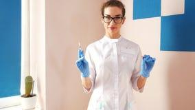 妇女医生注射器为射入做准备 有液体关闭的女性医生或护士藏品注射器 r 股票录像