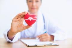 妇女医生画象有拿着的红色心脏,医疗保健骗局 免版税库存图片