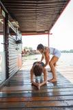 妇女协助锻炼的健身辅导员少妇胜过 免版税库存照片