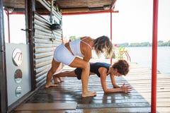妇女协助锻炼的健身辅导员少妇胜过 免版税库存图片