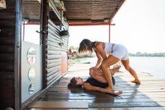 妇女协助锻炼的健身辅导员少妇胜过 免版税图库摄影