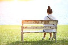 妇女单独坐一条长凳在公园 库存图片
