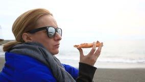 妇女单独坐在恶劣天气的一个离开的海滩,看海并且吃薄饼 股票录像