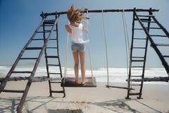 妇女单独摇摆在海滩 免版税库存图片