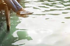 妇女单独河沿船坞休闲概念 免版税库存图片
