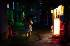 妇女单独走在雨季的夜街道 库存照片
