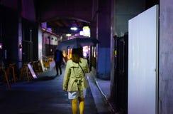 妇女单独走在雨季的夜街道 免版税库存图片