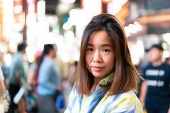 妇女单独走在雨季的夜街道 免版税库存照片