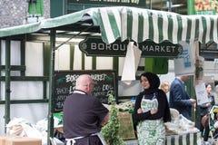 妇女卖围裙、茶巾和其他被说明的mercha 免版税图库摄影