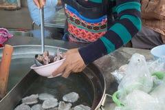 妇女卖在小船的面条在传统浮动市场上 免版税图库摄影