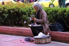 妇女卖在街道上的花 免版税库存图片