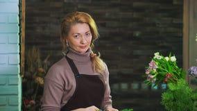 妇女卖花人洗涤从杉木针的冷杉分支准备花束 查看照相机