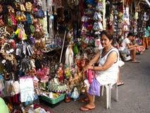 妇女卖被分类的宗教项目给她的摊位的游人在教会旁边 库存图片