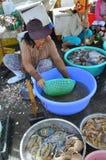 妇女卖鲜鱼在荣市Luong口岸的一个地方海鲜市场上 免版税库存照片