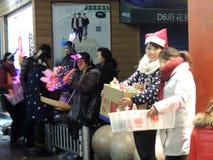 妇女卖主在戴圣诞老人圣诞节帽子的中国 免版税库存图片