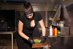 妇女厨师在准备汉堡包三明治的厨房里 免版税库存图片