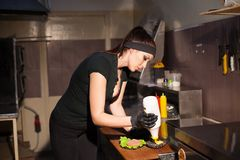 妇女厨师在准备汉堡包三明治的厨房里 免版税库存照片