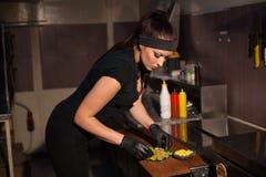 妇女厨师在准备汉堡包三明治的厨房里 库存照片