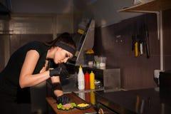 妇女厨师在准备汉堡包三明治的厨房里 免版税图库摄影