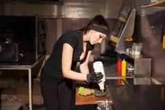 妇女厨师在厨房里准备一个汉堡 免版税图库摄影