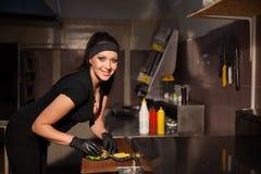 妇女厨师在厨房里准备一个汉堡 库存照片