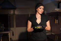 妇女厨师在厨房里准备一个汉堡 图库摄影