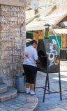 妇女厨师在市场上的一家小餐馆附近烹调在烤箱的蛋糕在老城英亩在以色列 免版税图库摄影