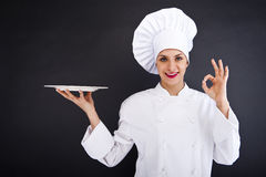 妇女厨师或主厨服务空的牌照的和微笑愉快 免版税图库摄影