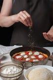 妇女厨师的手洒在黑暗的背景的意大利未加工的薄饼玛格丽塔酒oreano 在白色桌谎言成份o 免版税库存照片