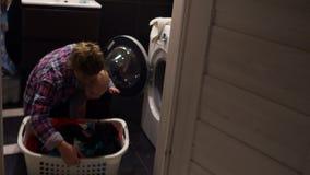 妇女去掉从洗衣机的洗衣店 她抱着她的她的胳膊的婴孩 应付她是很难的 股票录像
