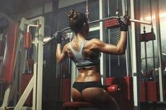 妇女参与在健身房的模拟器 图库摄影