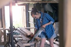 妇女参与处理木头在家庭车间,木匠业 免版税图库摄影