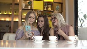 妇女友谊 看在智能手机的女性朋友照片,当咖啡休息时 股票录像