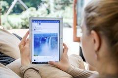 妇女发射在联想片剂的facebook应用 免版税库存图片