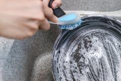 妇女发射有一把蓝色刷子的一个被烧的平底锅在厨房水槽 免版税图库摄影
