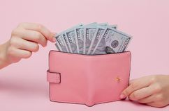 妇女取消金钱的` s手从在桃红色背景的钱包与拷贝空间 图库摄影