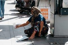 妇女叫化子请求金钱 免版税图库摄影