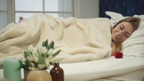 妇女叫醒了与一件礼物的早晨在床上 影视素材