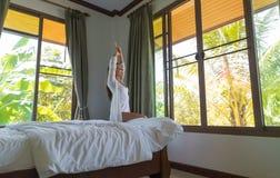 妇女叫醒舒展早晨卧室内部窗口的旅馆客房女孩 库存图片