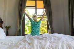 妇女叫醒舒展早晨卧室内部窗口的旅馆客房女孩 免版税库存照片