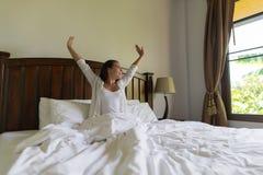 妇女叫醒舒展早晨卧室内部窗口的旅馆客房女孩 免版税库存图片