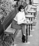 妇女可爱的浅黑肤色的男人吃食家蛋糕咖啡馆大阳台背景 烹饪享受 女孩放松与蛋糕的咖啡馆 免版税库存图片