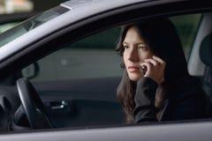 妇女司机坐的聊天在她的机动性 免版税库存照片